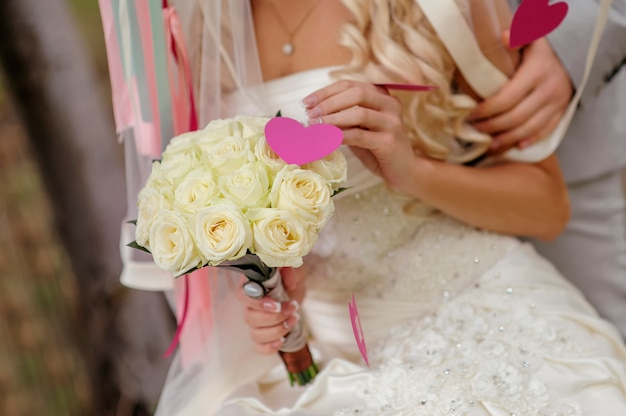 Wedding bouquet in hands of the bride of roses.