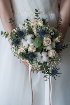 Wedding bouquet in the hands of the bride