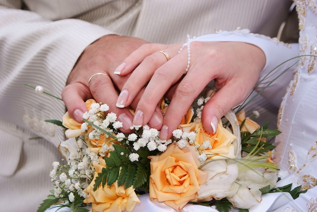 Wedding bouquet and hands with rings