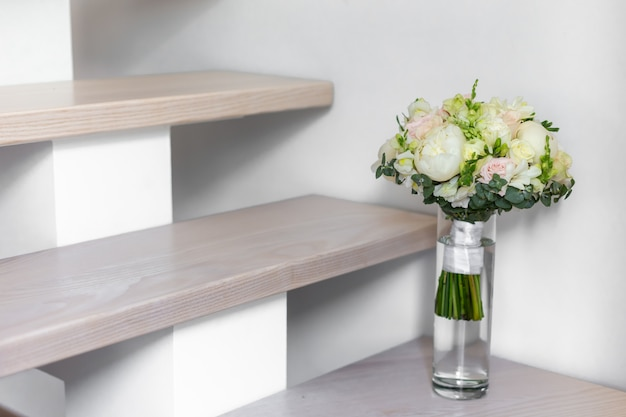 壁の近くの階段にあるガラスの花瓶のウェディングブーケ。