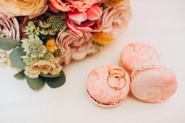 秋の色、結婚指輪、白いテーブルの上のマカロンのウェディングブーケ。