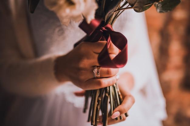 Свадебный букет в руках невесты в белом платье