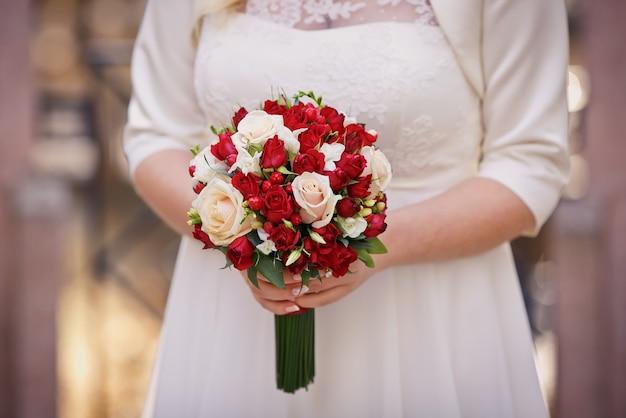 花嫁の手にウェディングブーケ Premium写真