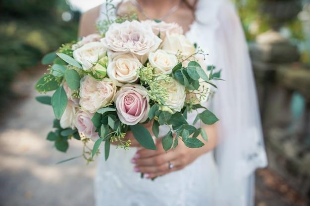 花嫁の手にウェディングブーケ。ウェディングドレスの花嫁の手に豪華な花束。