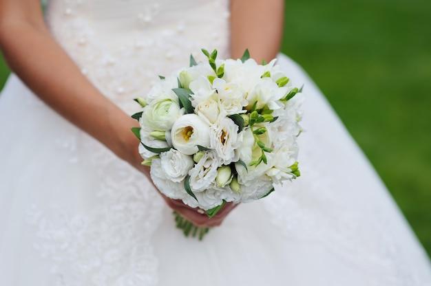 Свадебный букет в руках невесты.