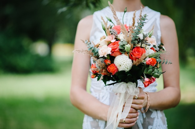 붉은 꽃 장미와 신부의 손에 웨딩 부케