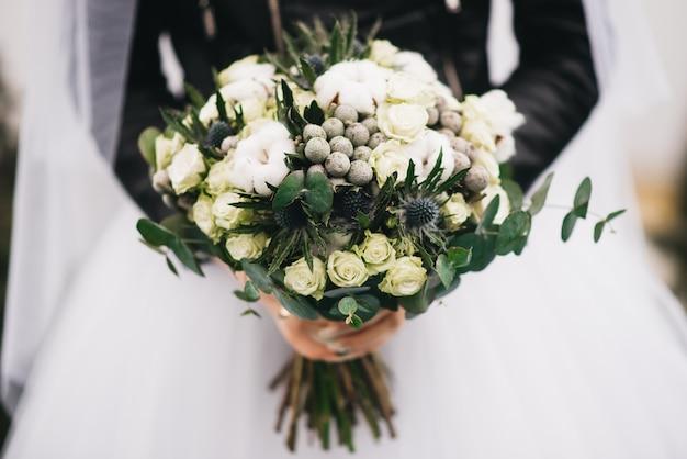 花嫁の手の中のウェディングブーケ。白いバラ、綿、いばら、緑のヒムキブーケ