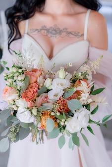 Eustoma와 유칼립투스로 만든 웨딩 부케, 가슴에 열린 데 콜테와 문신이있는 신부 드레스