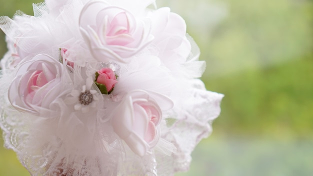 Wedding bouquet made of white roses on a blurred green background