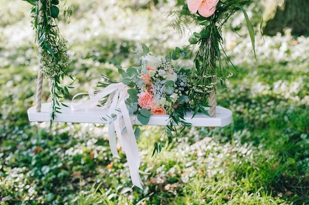 Свадебный букет из бежевых и розовых роз на открытом воздухе на украшенном качели