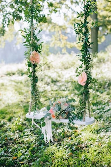 Свадебный букет из бежевых и розовых роз на открытом воздухе на украшенных качелях