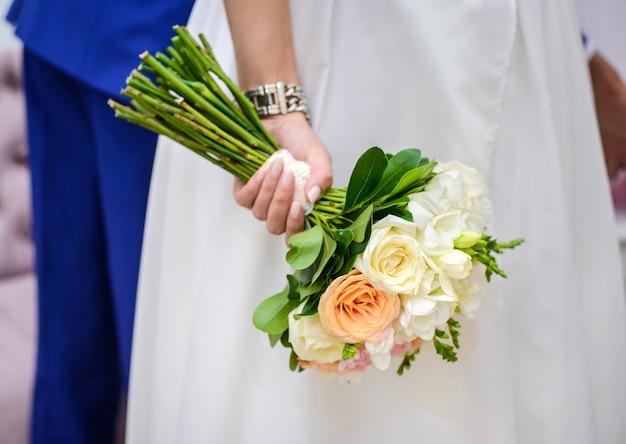 Свадебный букет из бежевых роз в руке невесты крупным планом