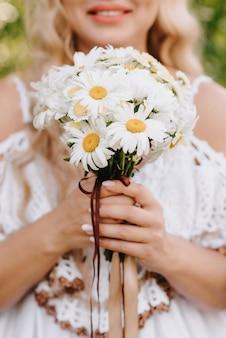 Свадебный букет ромашек в руках невесты на фоне белого платья