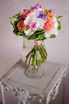 花、牡丹、バラのウェディングブーケは、テーブルの上の水の鍋に立っています