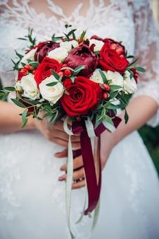 신부의 손에 신선한 꽃의 웨딩 부케, 자른 이미지, 클로즈업. 백색과 빨강 장미 꽃다발을 들고 젊은 신부.