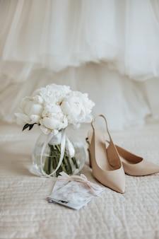 Свадебный букет из цветов пионов в вазе стоит на ложе молодоженов с приглашениями и туфлями на пространстве платья невесты.