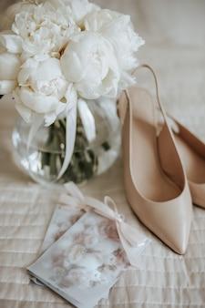 花瓶に牡丹の花のウェディングブーケが新婚夫婦のベッドの上に立っており、花嫁のドレスのスペースに招待状と靴があります