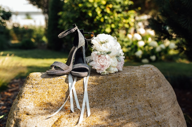 石の上の女性の靴の横にある牡丹のウェディングブーケ。