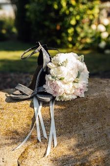 Свадебный букет пионов рядом с женской обувью на камне.