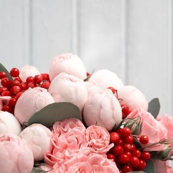 Свадебный букет из пионовидных кустовых роз с ягодами калины на белом фоне.