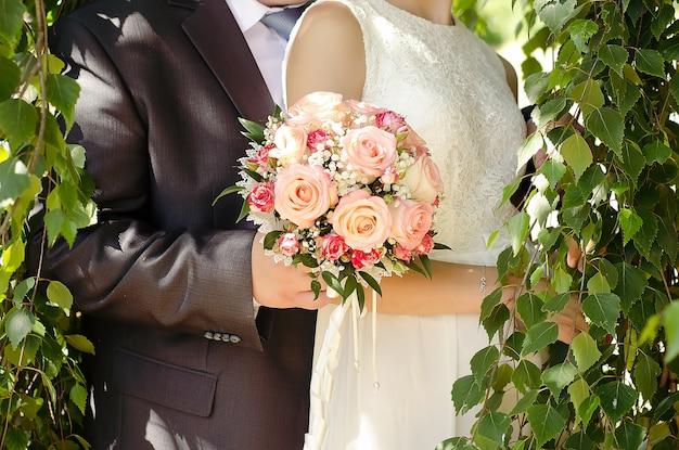 Свадебный букет из розовых роз в руках жениха и невесты крупным планом
