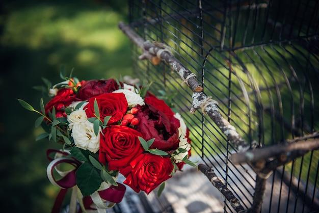 Свадебный букет из красных и белых роз на солнце на открытом воздухе