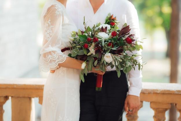Свадебный букет из красных цветов и зелени в руках жениха и невесты
