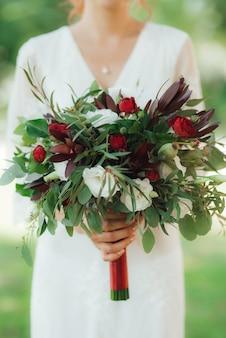Свадебный букет из красных цветов и зелени в руках невесты