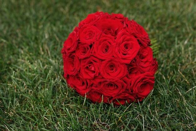 緑の草の上の赤いバラのウェディングブーケ