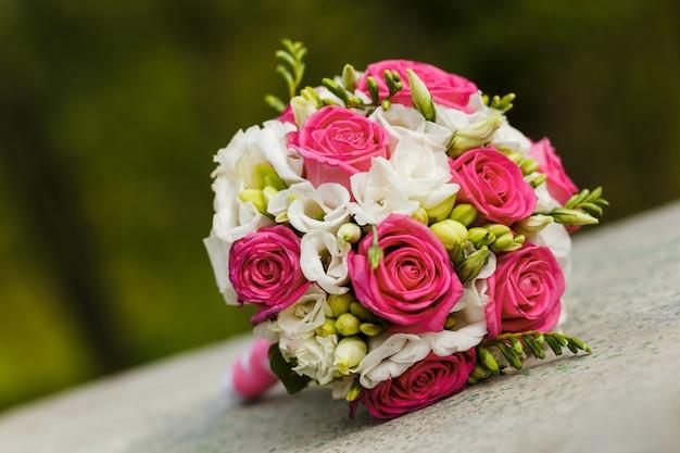 Свадебный букет из красных белых роз, лежащих на камне
