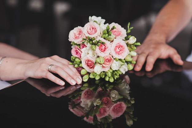 バラのウェディングブーケと新婚カップル。結婚式の日