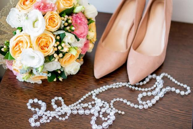 ベージュの靴の横にあるバラのウェディングブーケ