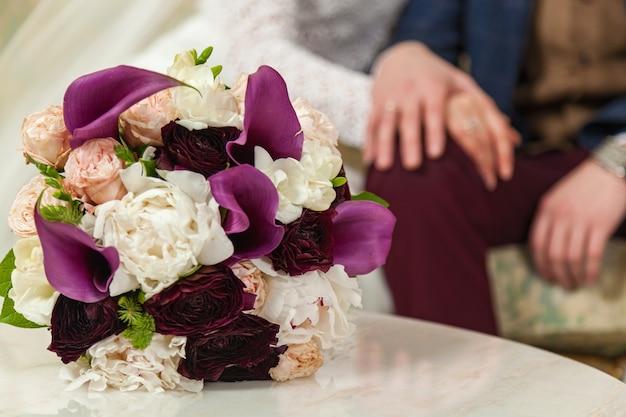 白いテーブルの上のバラのウェディングブーケ
