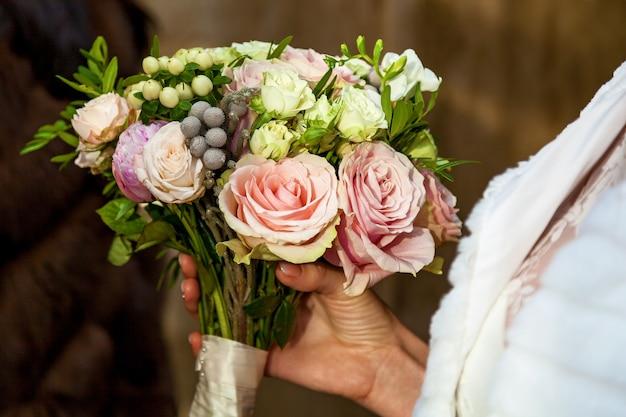 花嫁の手にピンクのリボンが付いたバラのウェディングブーケ、花嫁はバラのウェディングブーケを持っています