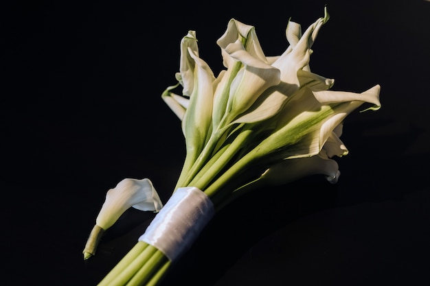 Свадебный букет из белых лилий каллы на черном фоне
