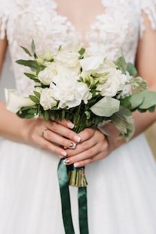 드레스의 배경에 신부 손에 흰 장미 웨딩 부케