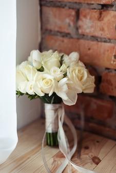 Свадебный букет из белых роз на кирпичной стене