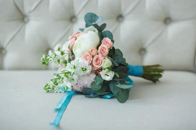 가벼운 소파에 청록색 리본이 달린 흰 장미, 분홍색 장미 및 모란의 웨딩 부케.