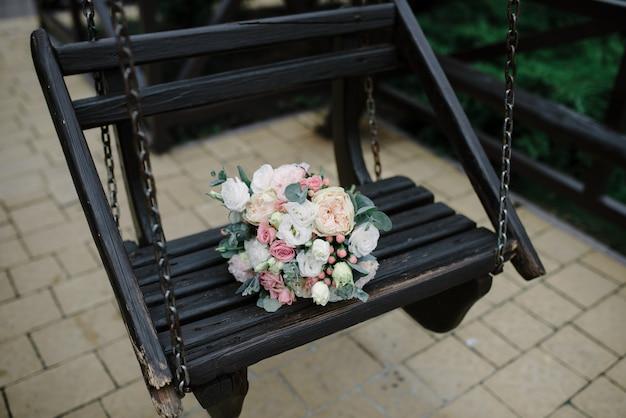 Свадебный букет на старых деревянных качелях