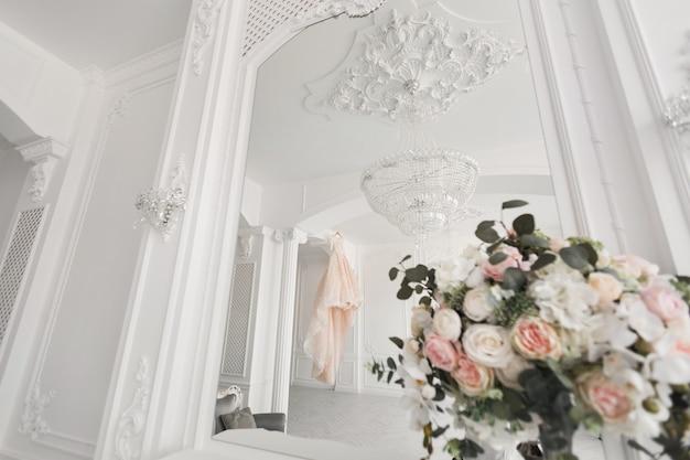 ハンガーの上の豪華なウェディングドレスの背景にウェディングブーケ