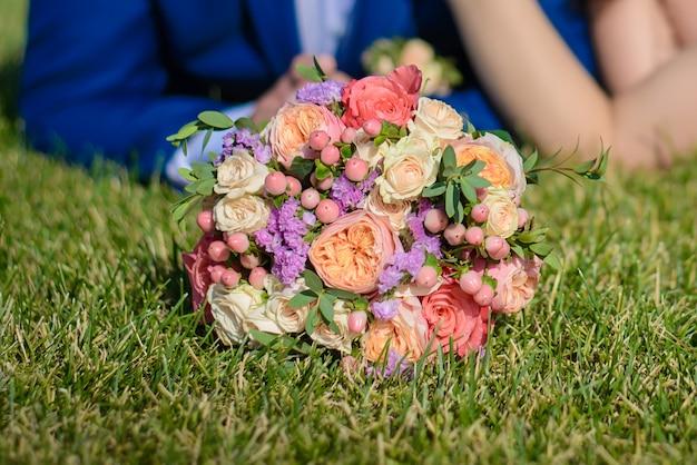 Свадебный букет на траве у жениха и невесты
