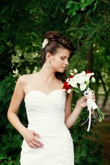ウェディングブーケウェディングメイクとウェディングヘアスタイルの美しい幸せな花嫁の肖像画