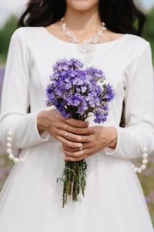 Wedding bouquet of purple wildflowers in the hands of the bride on the background of a white dress