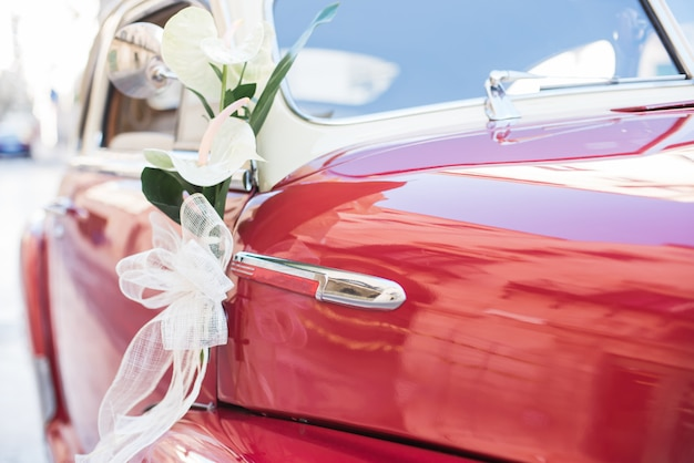 Wedding bouquet on red vintage wedding car.