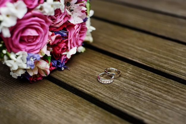 Wedding bouquet and rings on wooden background