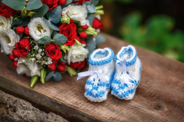 Wedding bouquet of roses and baby booties on wooden surface
