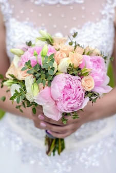 Wedding bouquet of roses and peonies in the hands of the bride