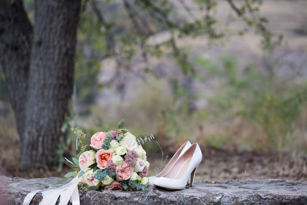 Wedding bouquet of roses and shoes close-up.