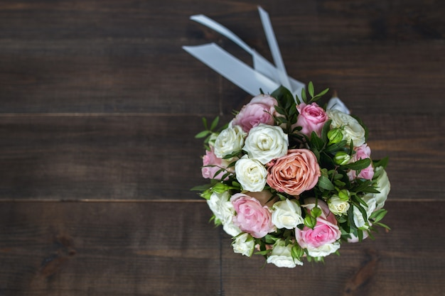 Wedding bouquet of roses on a wood
