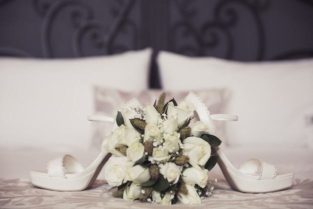 Wedding bouquet and shoes on bedroom